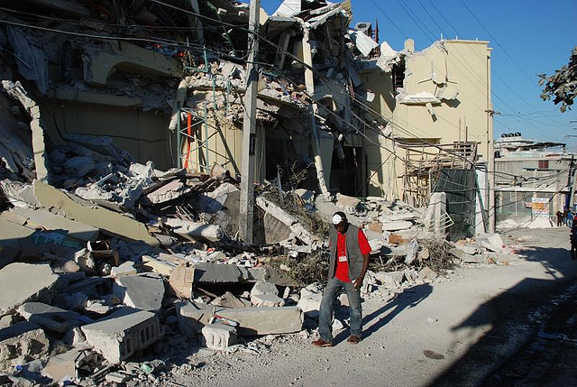 Man walking past earthquake rubble.