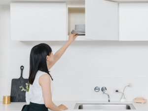 Marie Kondo reaches for dishes in a minimalist kitchen