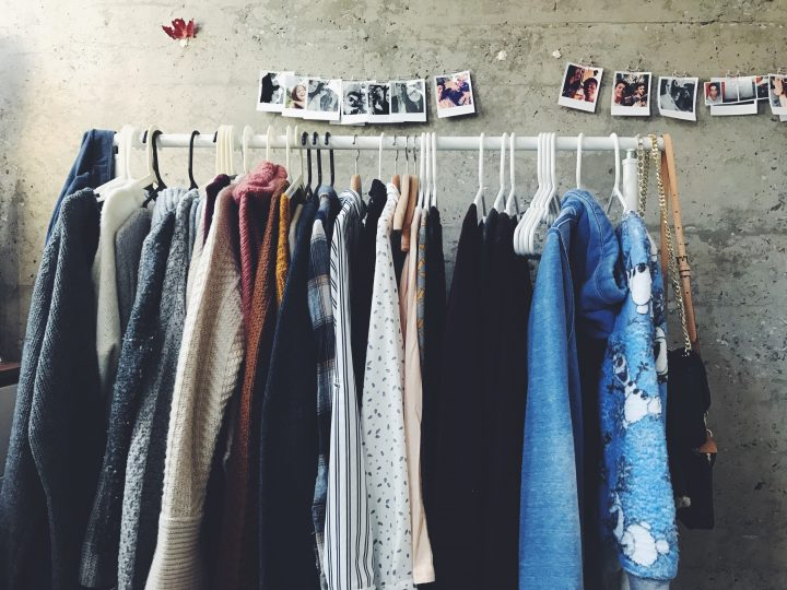 A variety of clothing hanging from a clothes hanger, under a set of polaroid pictures