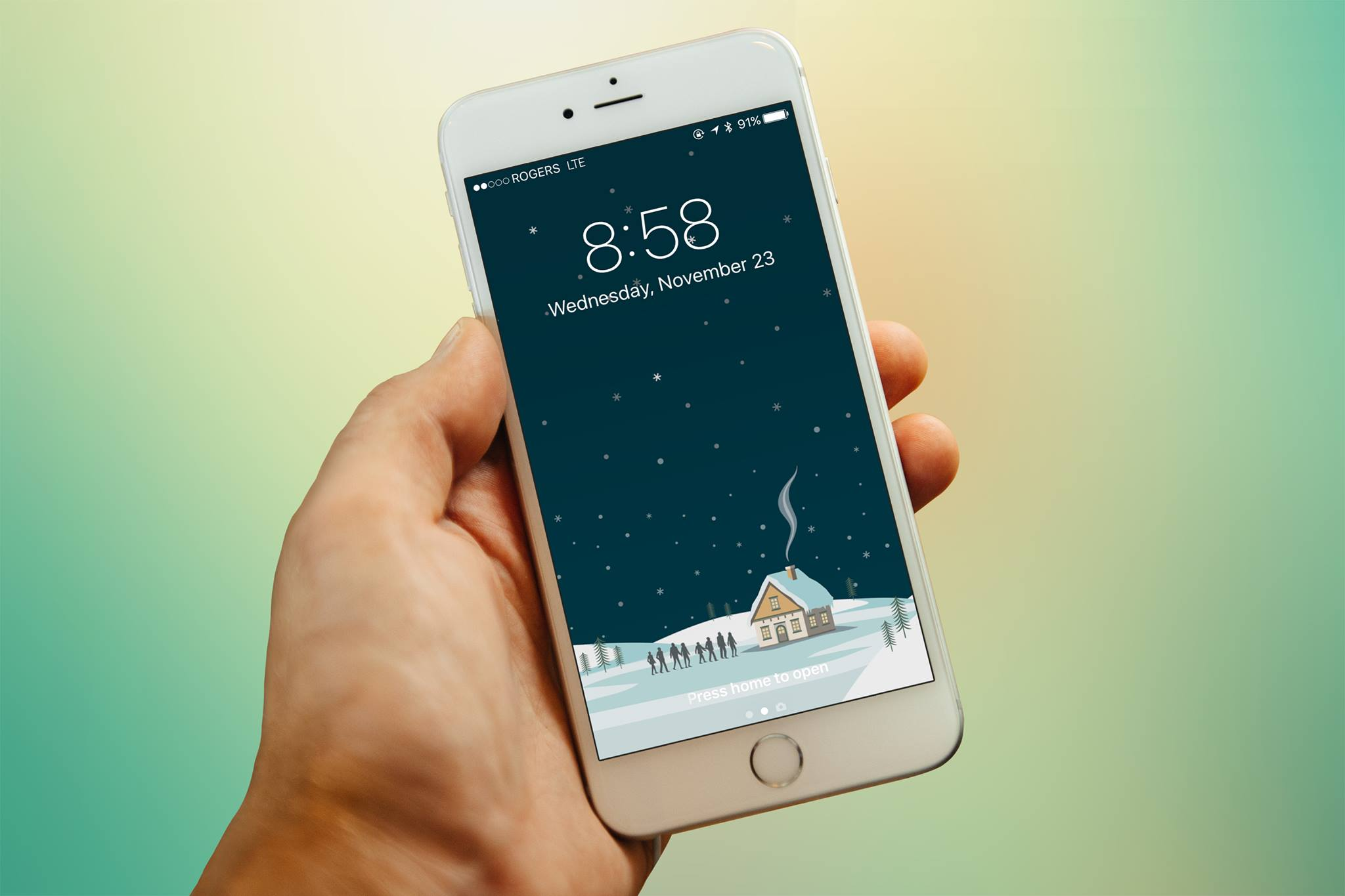 Hand holding an iPhone 6 displaying our latest Christmas wallpaper!