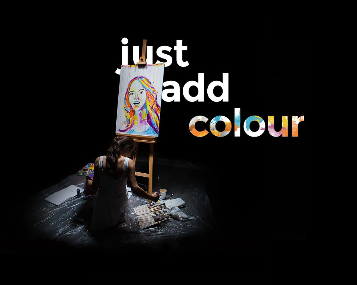Just Add Colour – A picture of a girl in a dark room working on a colourful paint