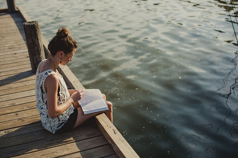 Picture of a girl sitting on a pier and reading the Bible on a sunny day.
