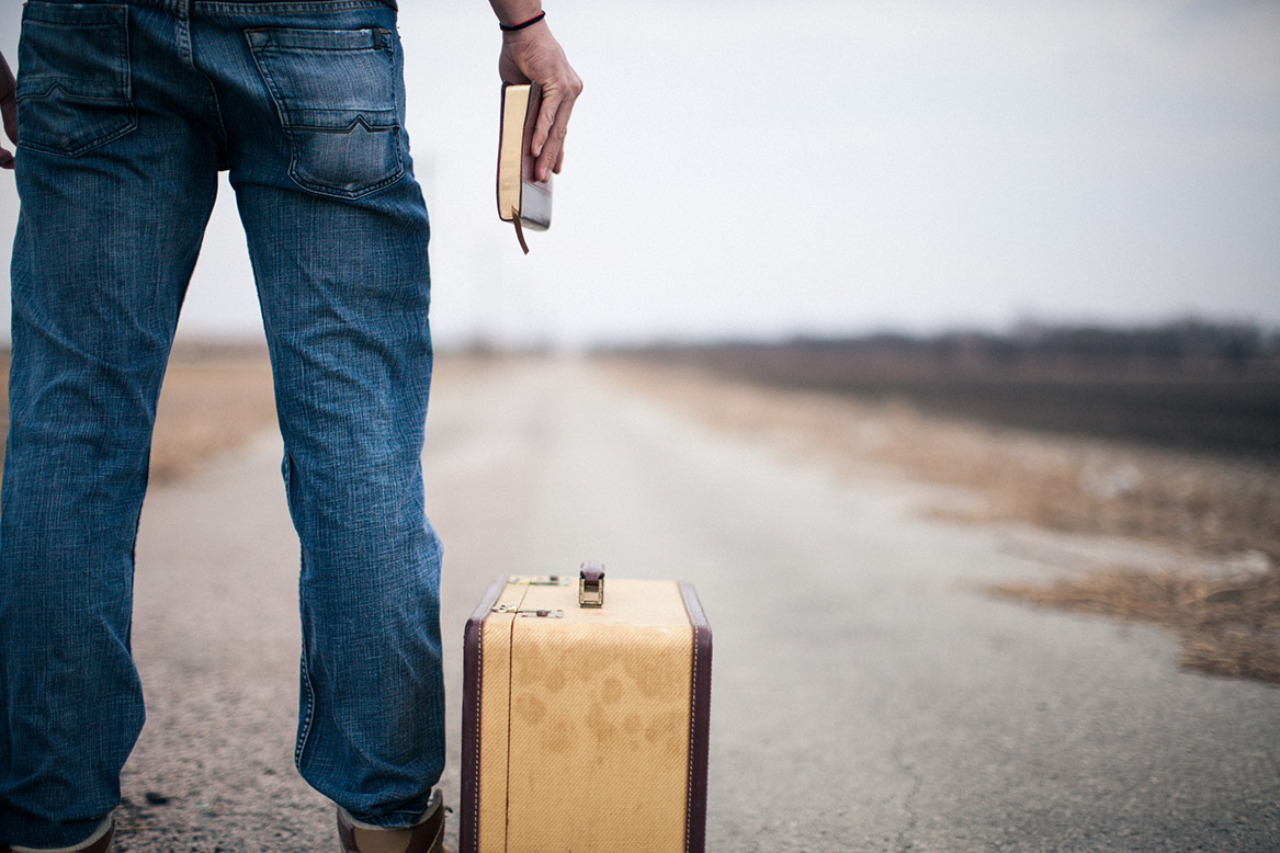 Man starting at a road with his luggage by his side and a bible on his hand.