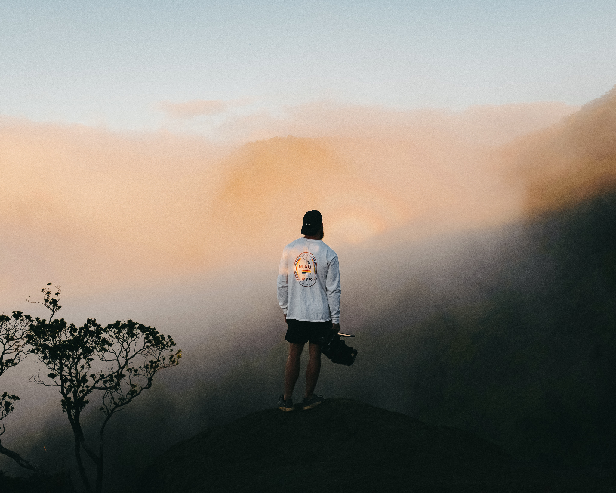 A young man stands on a mountain, overlooking a foggy valley. He can't see what's in ahead of him.